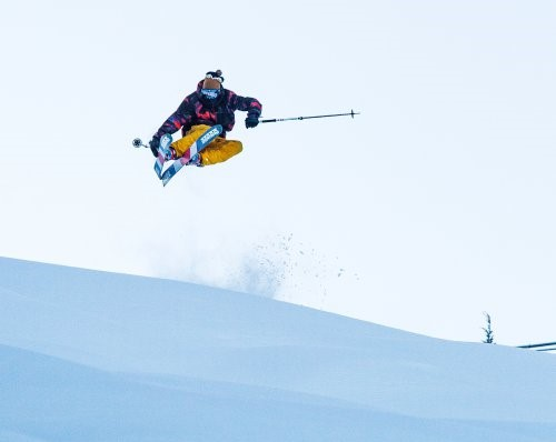 A person jumping in the air while downhill skiing - NTN Bindings