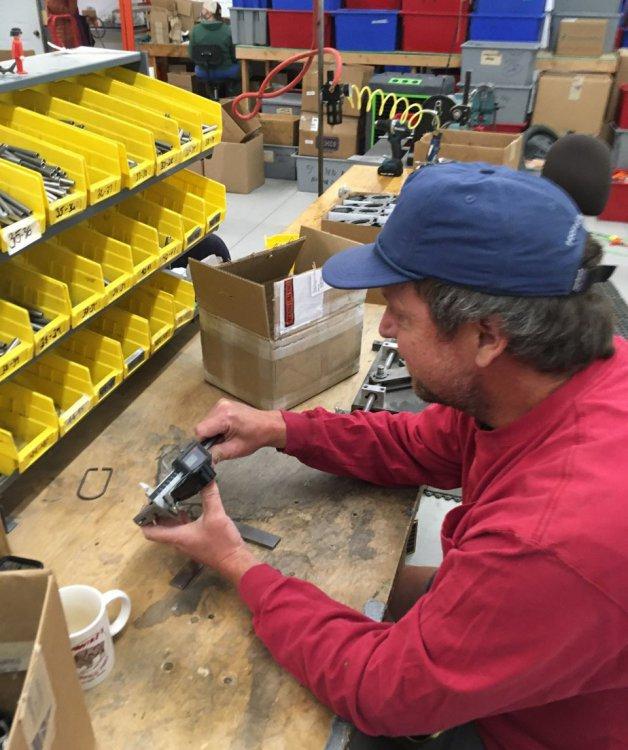 A man in a shop working on Telemark Ski Bindings