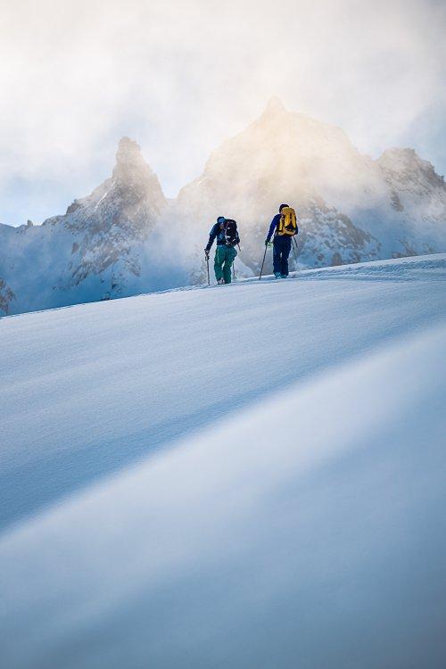 Two people downhill skiing in fresh powder - Telemark Bindings